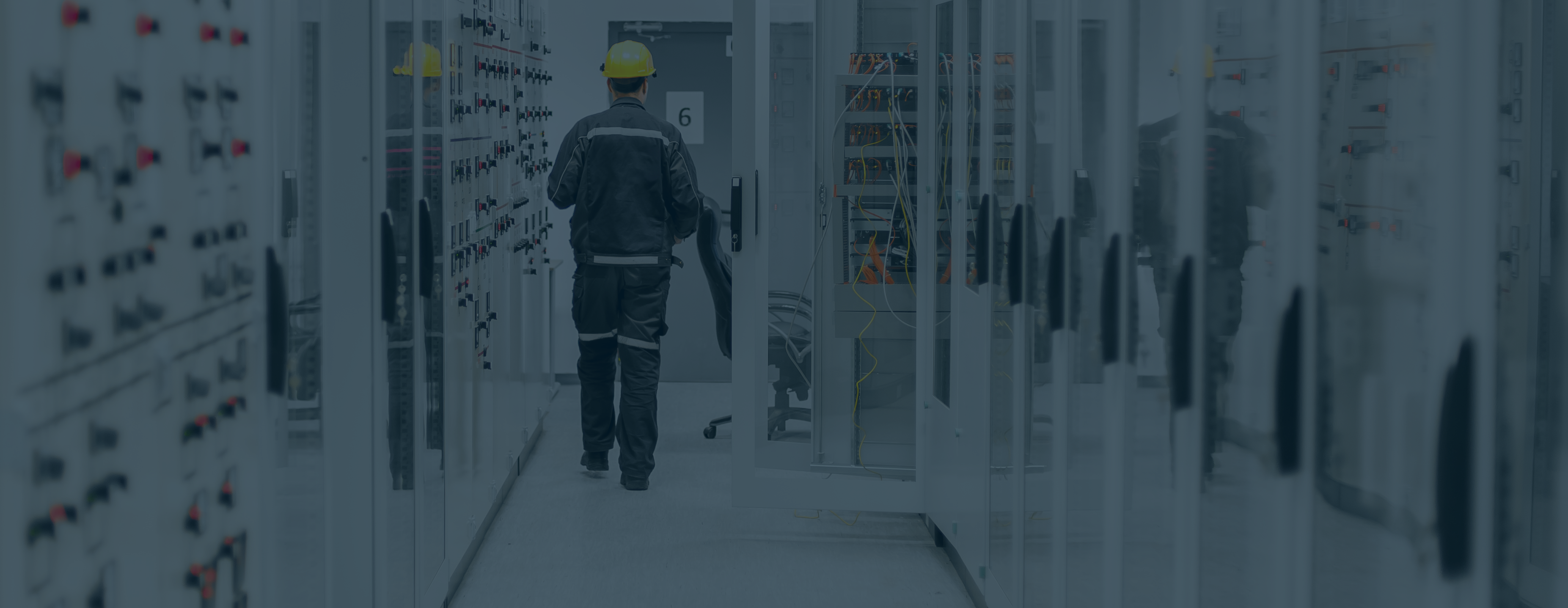 Medium voltage switchgear equipment with man in protective gear walking in background